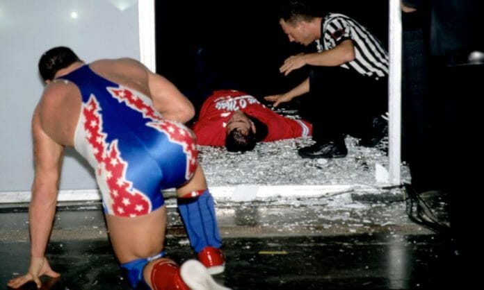 Kurt Angle Kneeling after throwing Shane McMahon through glass at King of the Ring (2001) Angle laying on the ground in broken glass and a referee kneeling beside him