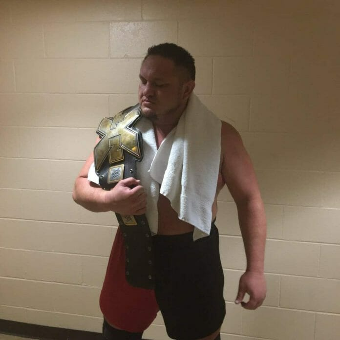 Samoa Joe poses backstage with the NXT championship belt on his shoulder and a white towel around his neck after defeating Finn Balor in Lowell, Massachusettes at a house show, April 21, 2016.