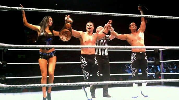 Primo and Epico in black and white wrestling tights holding their hands up with the title belt and a ring girl to celebrate winning the Tag Team Championship from Air Boom in Oakbank, California, January 15. 2012