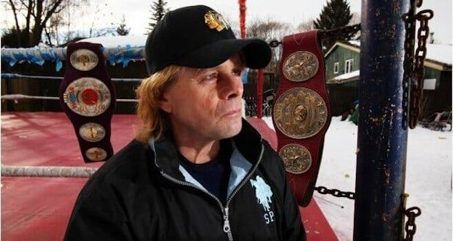 Bruce Hart in a black baseball cap and jacket next to an outdoor ring with 2 title belts hanging on the ropes