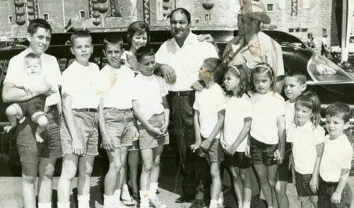 Bruce Hart and his family visit the Calgary Stampede with Rocky Marciano, former world heavyweight boxing champion, on July 8, 1964. Left to right: Smith, holding baby Diana; Bruce; Keith; Helen, Wayne; Rocky Marciano; Dean; Ellie; Stu; Georgia; Bret; Alison and Ross. Owen was born the next year. (Source unknown, provided courtesy Alison Hart, with thank to SLAM! Pro Wrestling)