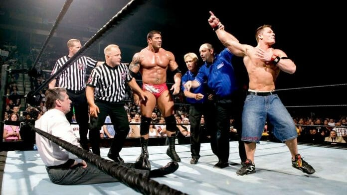 Vince McMahon sits angrily on the ring canvas after tearing both quads by entering the ring at the 2005 Royal Rumble pay-per-view event while four referees, Dave Bautista and John Cena stand nearby