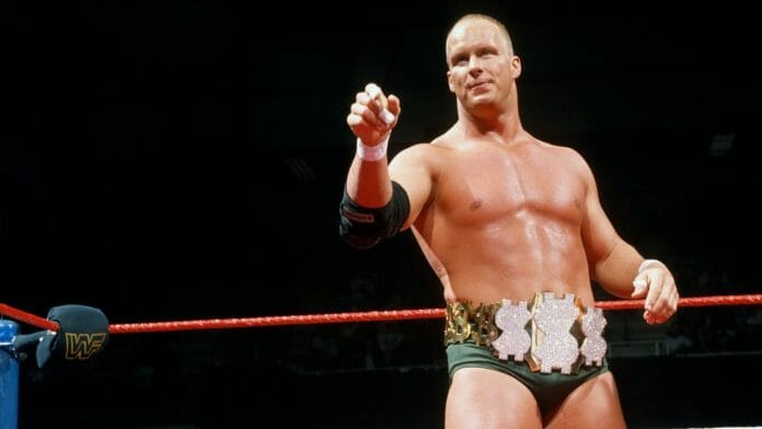 Steve Austin in the ring with green wrestling trunks and a belt with 3 dollar signs on the front