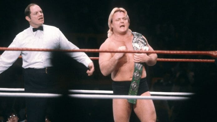 Greg Valentine in a dim-lit wrestling ring holding his green leather Intercontinental Championship belt with a referee behind him