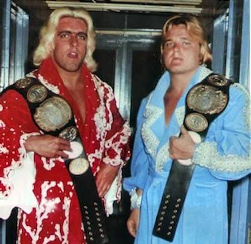 Greg Valentine wearing a blue robe and Ric Flair wearing a red robe with their Mid-Atlantic NWA World Tag Team Titles hung around their shoulders