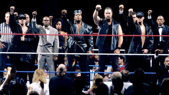 Gang Wars - The original iteration of The Nation of Domination featured in a wrestling ring with their right fists raised