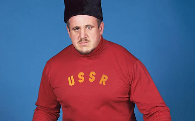 A photo of Nikolai Volkoff wearing a red long-sleeved shirt with USSR written on it in yellow, and a black Soviet hat with blue background.