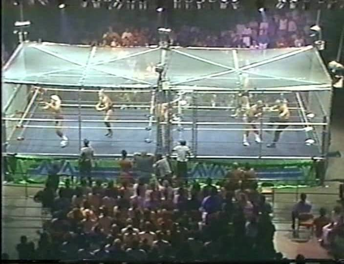 A faded color photo showing two steel cages side by side for the first ever War Games match at the Omni Coliseum, July 4, 1987