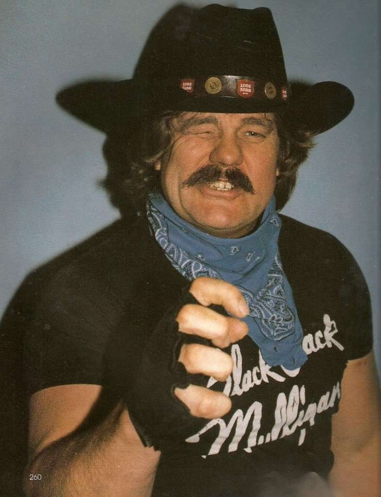 Blackjack Mulligan wearing a black cowboy hat, a blue bandana around his neck , a black glove on his right hand with holes where his fingers come through and a black t-shirt which reads 'Blackjack Mulligan'