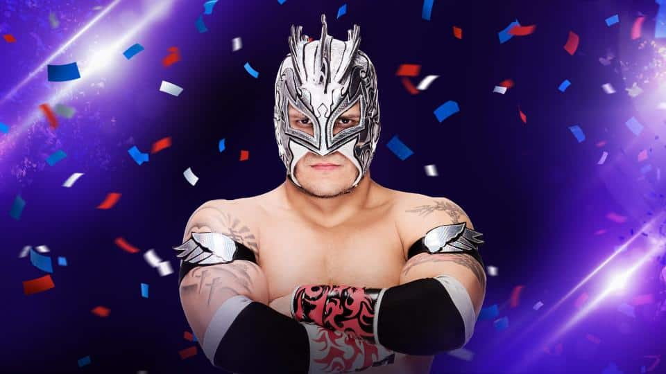 Kalisto - with a white and silver luchadore mask on with red, white and blue confetti flying around him with a purple backdrop