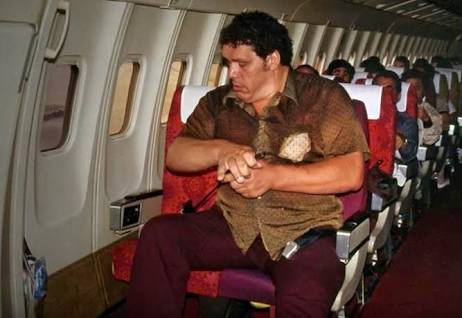 Andre the Giant Documentary | 12 Things Learned (And Facts Left Out!) - Andre the Giant sitting uncomfortably in the front row of an international flight