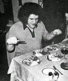 Andre the Giant Documentary | 12 Things Learned (And Facts Left Out!) - Black and white photo showing Andre with four full plates of food in front of him on a table
