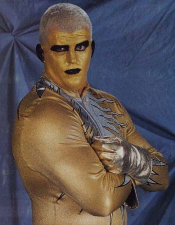 Goldust in 1996 wearing short-trimmed, white hair, a gold and white outfit with gold gloves and gold face paint