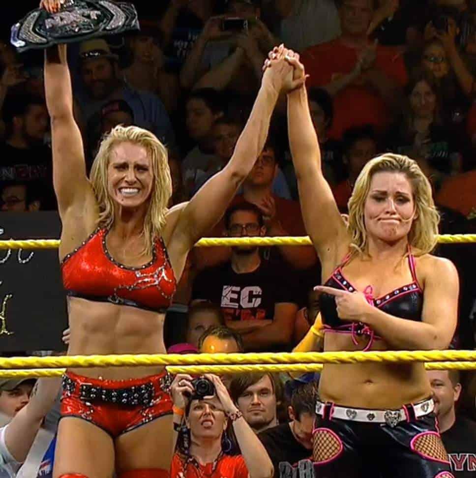 Reid Flair's sister Charlotte is overcome with emotion as Natalya raises her hand in victory after winning the NXT Women's Championship at the inaugural NXT TakeOver on May 29, 2014