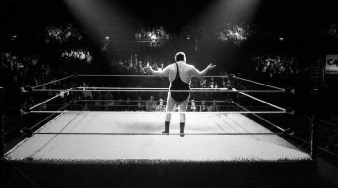 Andre the Giant Documentary | 12 Things Learned (And Facts Left Out!) - Black and white photo of Andre taking in the crowd's reception in the center of a wrestling ring with lights shining on him
