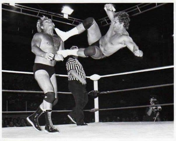Black and white photo of Curt Hennig hitting a dropkick on Nick Bockwinkel in AWA