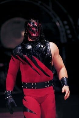 In October 1998, Kane would revert back to his old gear, one sleeve, and stitching, whilst maintaining the new elongated flame design