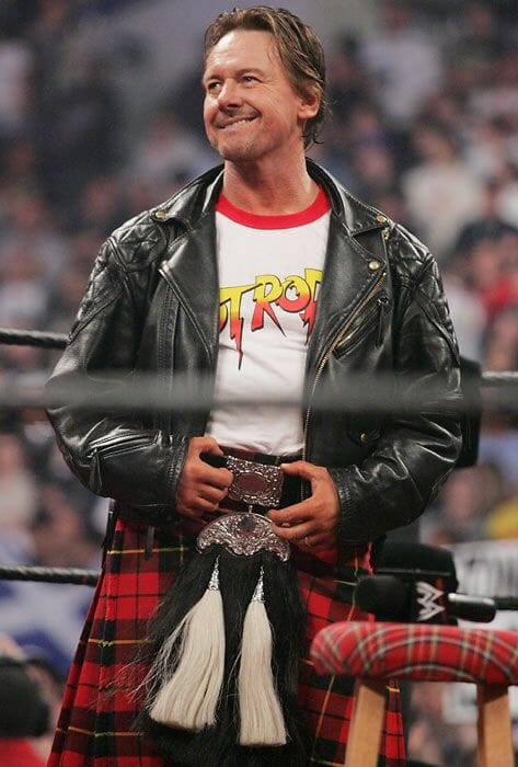 Roddy Piper in a leather jacket with a Piper's Pit shirt on