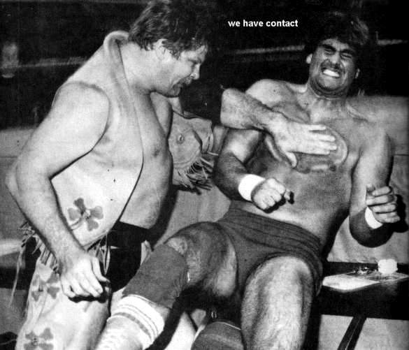A black and white photo of Stan Hansen laying in a stiff left-hand chop to Tom Zenk
