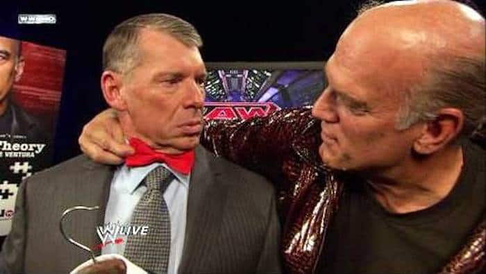Jesse Ventura puts a red bow tie on Vince McMahon during his appearance on Monday Night Raw as guest host in 2009