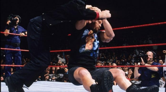 Steve Austin delivers a stunner to Mr. McMahon. The Austin and McMahon rivalry was one of the most iconic feuds in sports entertainment.