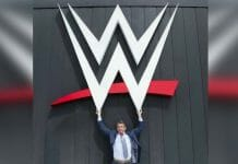 Vince McMahon stands proudly underneath the current WWE logo