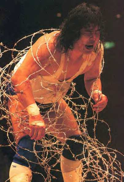 Atsushi Onita wrapped in barbed wire and in a lot of pain.