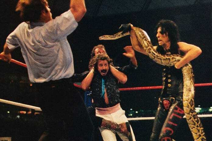 Alice Cooper spooks the referee with Damien the Snake at WrestleMania III while Jake Roberts applies a Full Nelson on Jimmy Hart.