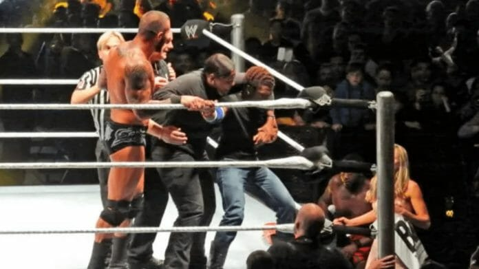 The fan being escorted as Randy Orton watches on.