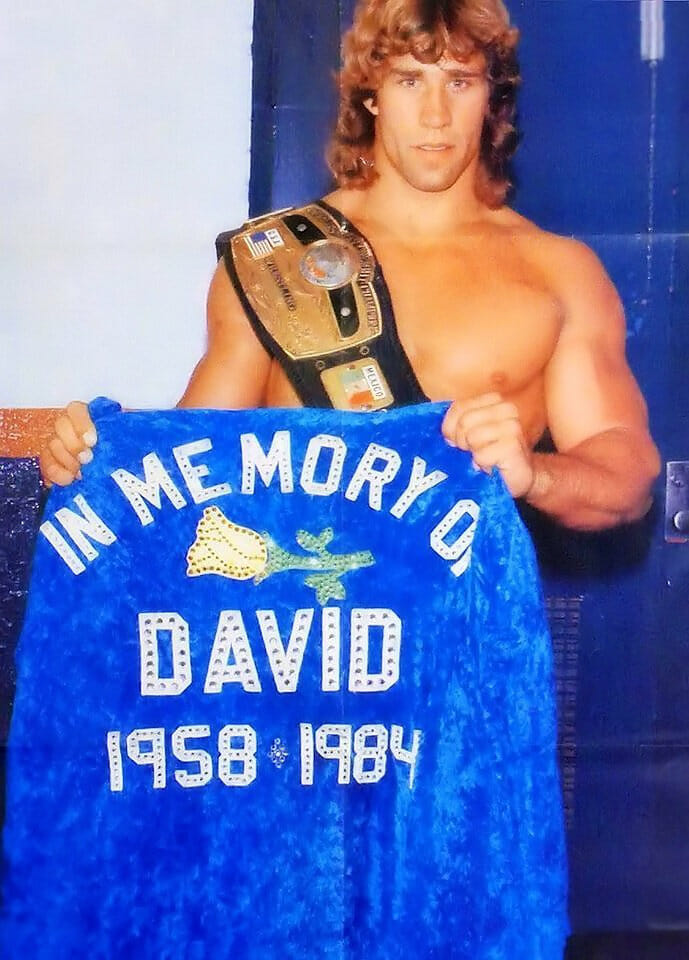 Kerry Von Erich holds up a jacket honoring the memory of his brother David after becoming NWA World Heavyweight Champion.