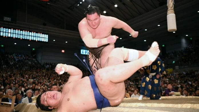 Hakuho throws down Tochiozan at a Grand Sumo Tournament in Osaka on March 17, 2019. [Photo by Tomoki Mera]