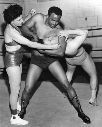 In 1967, Mae Young opened a wrestling school at the Olympic Auditorium in Los Angeles. At the time, women's wrestling had only been legal in California for a year and a half. Here she is seen with pupils Samuel Lewis and Raul Rivera.