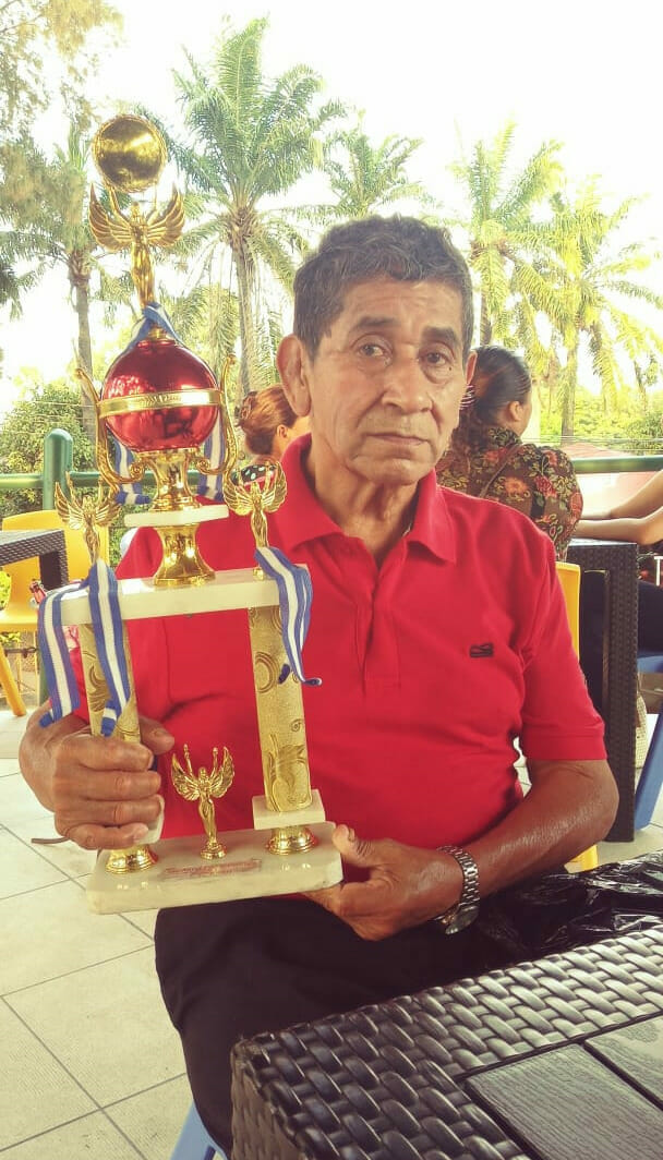 Al Capotes shows off one of the many wrestling trophies he had won during his storied career.