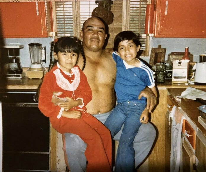 Paloma and her brother sit on their proud father's lap. This was a side of the dreaded Great Goliath the fans at the time would never have fathomed existed.