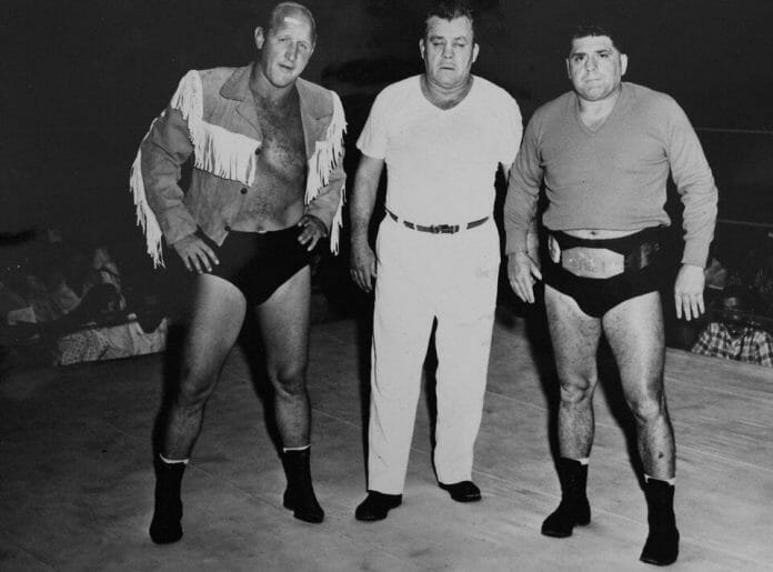 A 1950 photo of Angelo Savoldi, right, wearing his NWA Junior Heavyweight Championship belt, while standing in the ring in Amarillo, Texas with fellow wrestler Dory Funk Sr.